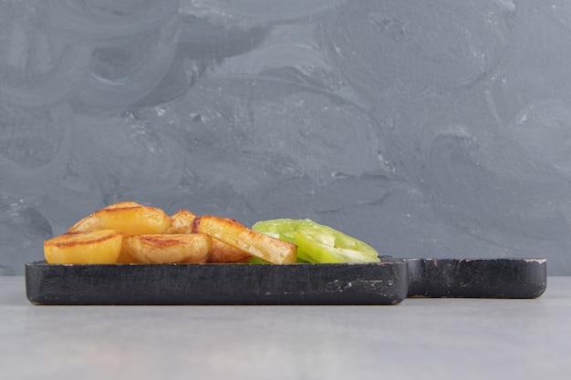 Fatias de batata frita e pimentão no quadro negro.