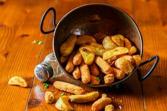 Fatias de batata frita no utensílio de cobre na mesa de madeira