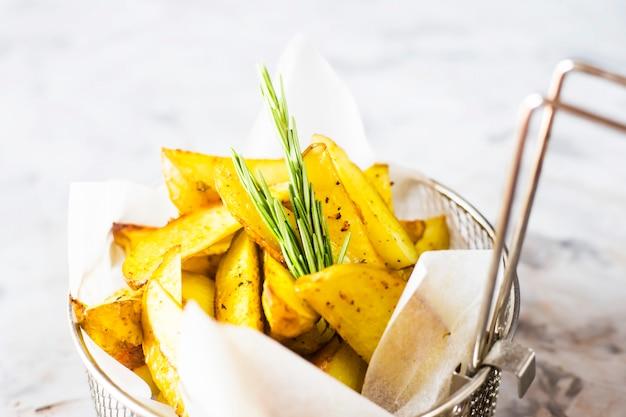 Fatias de batatas assadas com especiarias e alecrim em uma grade para fritar