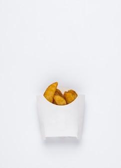 Fatias de batatas fritas em uma caixa branca sobre um fundo branco batatas fritas no fundo branco