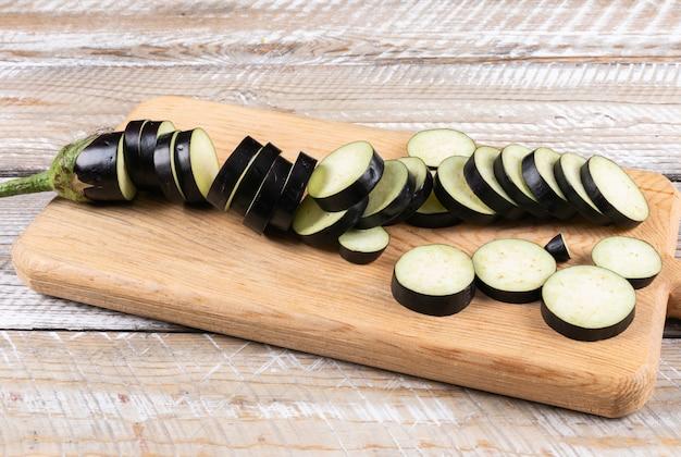 Fatias de berinjela em uma placa de corte vista de alto ângulo em um de madeira