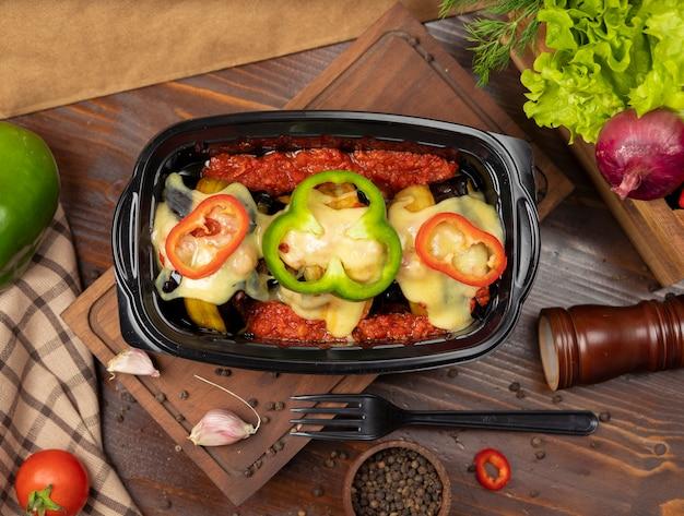 Fatias de berinjela grelhadas recheadas com carne e queijo derretido no topo com fatias de pimentão takeaway