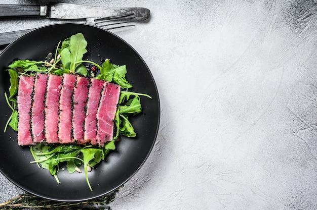 Fatias de bife de atum de peixe grelhado em um prato com salada de rúcula.