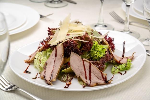 Fatias de bife grelhado com salada de folhas verdes em prato rústico com talheres. bife de churrasco mal passado e salada saudável