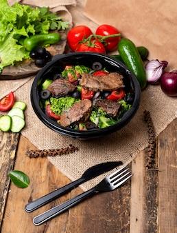 Fatias de bife grelhado com salada verde, tomate e azeitonas