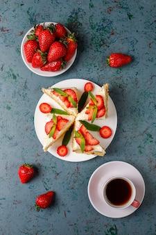 Fatias de bolo caseiro delicioso de morango com creme e morangos frescos, vista superior