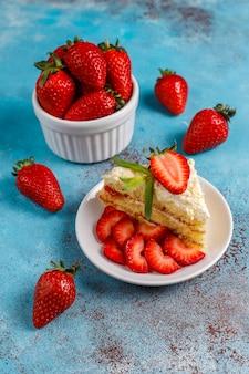 Fatias de bolo caseiro delicioso de morango com creme e morangos frescos