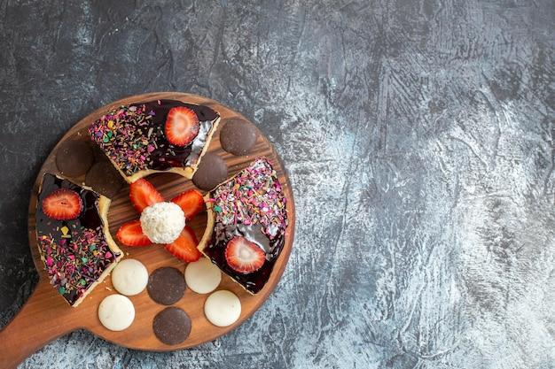 Fatias de bolo com biscoitos em superfície escura