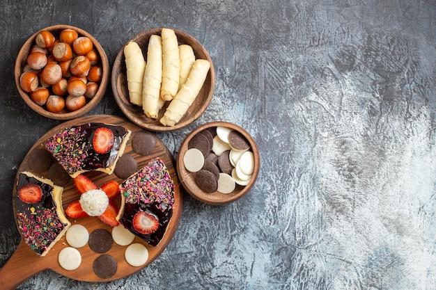 Fatias de bolo com nozes e biscoitos em superfície escura