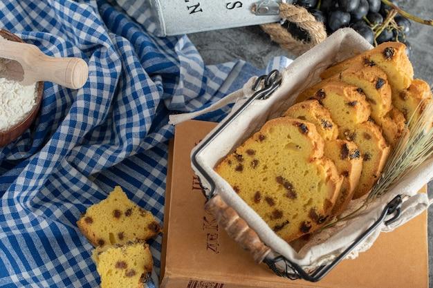Fatias de bolo com passas em cesta com uvas e toalha de mesa