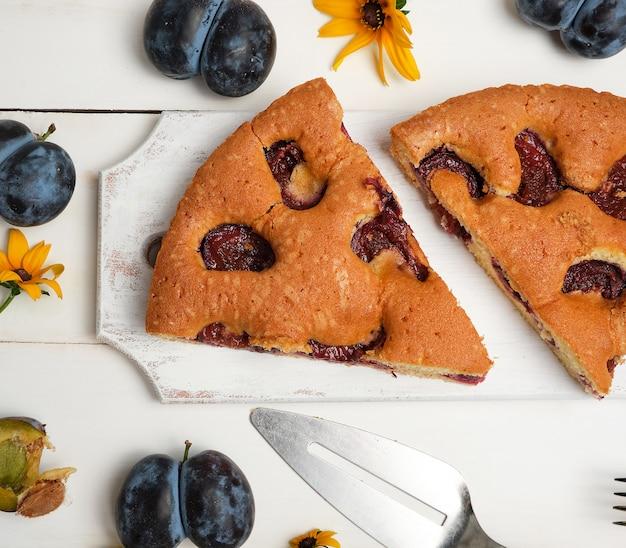 Fatias de bolo de ameixa biscoito em uma placa de madeira branca e frutas frescas