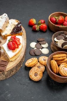 Fatias de bolo de frente com barras de chocolate e biscoitos em fundo cinza