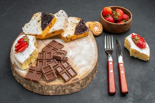 Fatias de bolo de frente com barras de chocolate e morangos em fundo cinza