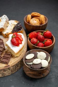Fatias de bolo de frente com biscoitos de frutas e barras de chocolate em fundo escuro
