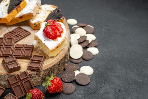 Fatias de bolo de frente com biscoitos e barras de chocolate em fundo escuro