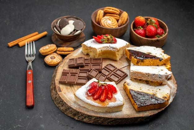 Fatias de bolo de frente com biscoitos e chocolate em fundo escuro
