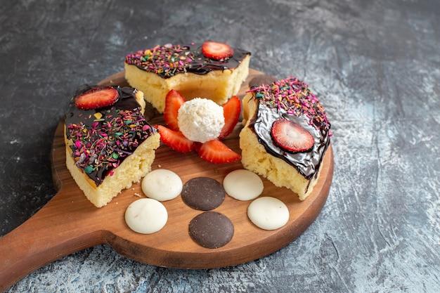 Fatias de bolo de frente com biscoitos em fundo escuro