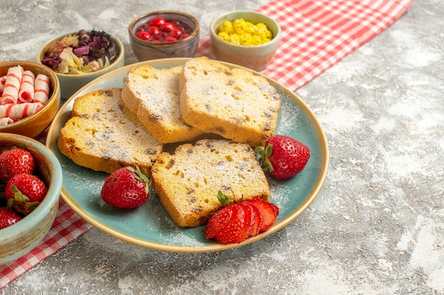 Fatias de bolo de frente com morangos frescos e doces em torta de frutas doces de superfície clara