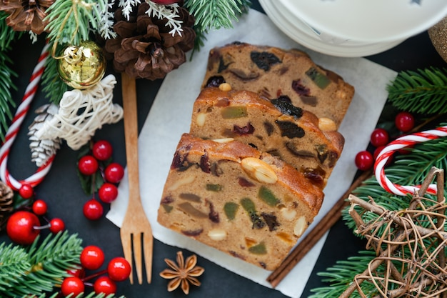Fatias de bolo de frutas doces em papel branco, colocar na mesa de granito preto em vista superior plana leigos com decoração de natal