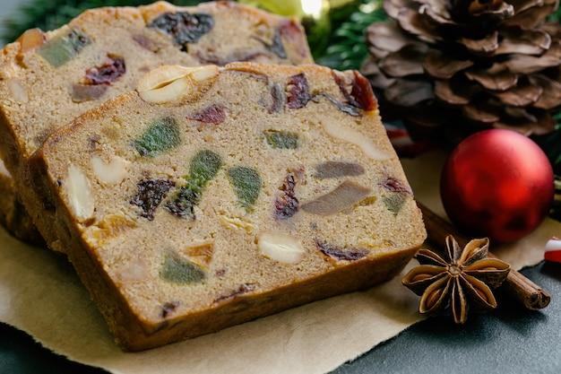 Fatias de bolo de frutas doces em papel pardo, colocar na mesa de granito preto em close-up vista com decoração de natal.