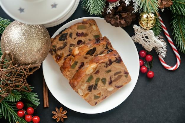 Fatias de bolo de frutas doces na chapa branca, colocar na mesa de granito preto na vista superior plana leigos com decoração de natal.