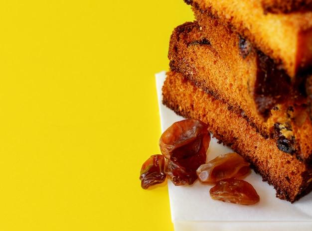 Fatias de bolo de frutas secas tradicionais para o natal pronto para comer com algumas passas em amarelo