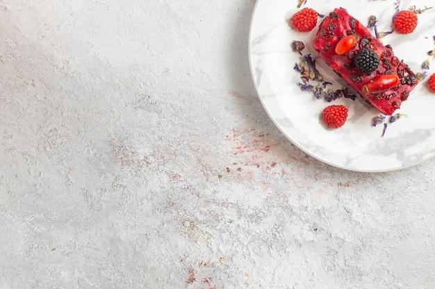 Fatias de bolo de frutas vermelhas com cobertura cremosa vermelha e frutas frescas na superfície branca