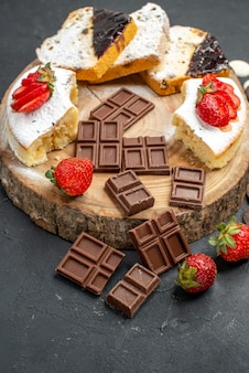 Fatias de bolo de meia vista com barras de chocolate e biscoitos em fundo escuro