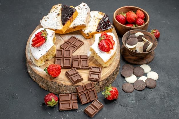 Fatias de bolo de vista frontal com barras de chocolate e biscoitos em fundo escuro