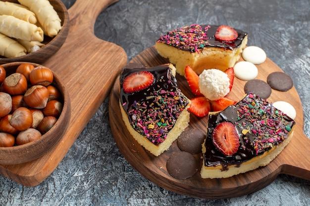 Fatias de bolo de vista frontal com nozes e doces em fundo escuro