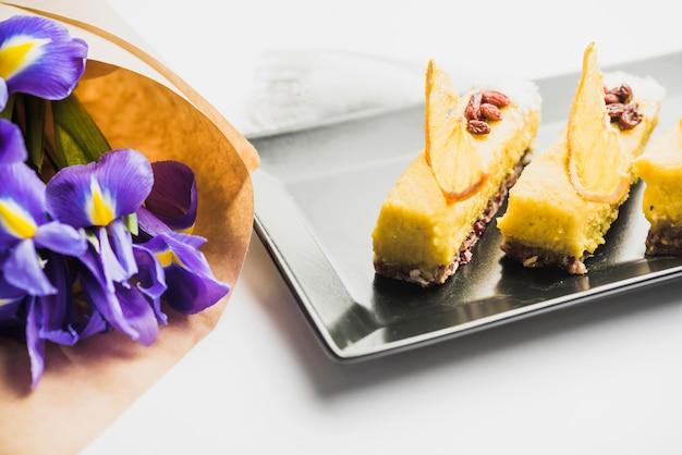 Fatias de bolo decorativas na bandeja e buquê de flores da orquídea