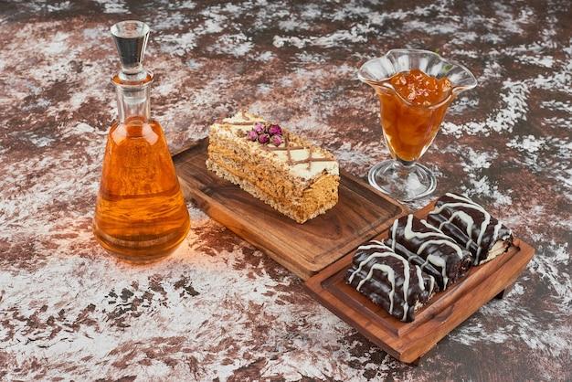 Fatias de bolo e confiture em uma placa de madeira.