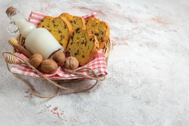 Fatias de bolo gostoso de vista frontal com leite e nozes na superfície branca