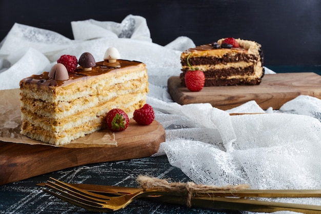 Fatias de bolo na placa de madeira com frutas ao redor.