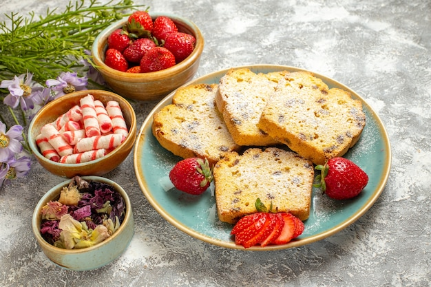 Fatias de bolo saborosas de frente com morangos em torta de bolo doce de superfície leve