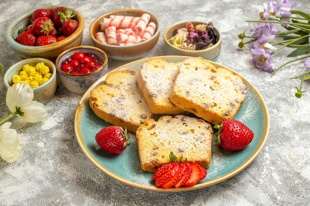Fatias de bolo saborosas de frente com morangos em tortas de bolo doce de frutas de superfície clara