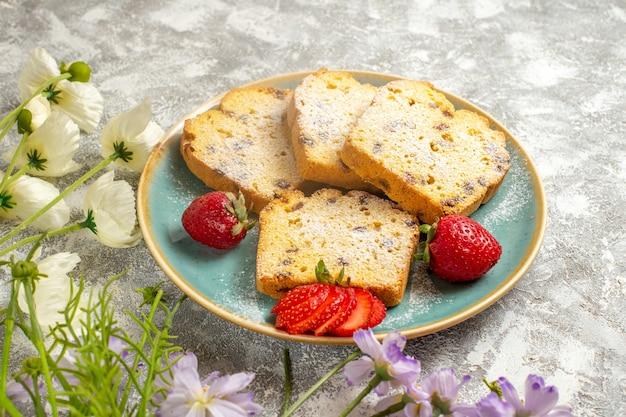 Fatias de bolo saborosas de frente com morangos na superfície clara