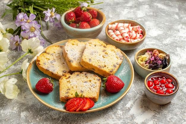 Fatias de bolo saborosas de frente com morangos na torta de bolo doce de frutas de superfície clara
