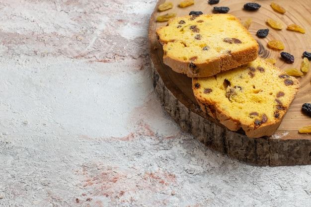Fatias de bolo saborosas de frente com passas na superfície branca