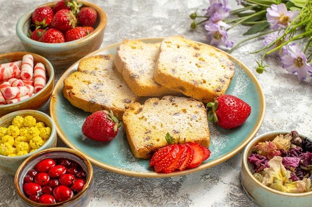 Fatias de bolo saboroso com morangos na superfície clara e torta de bolo doce