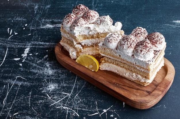 Fatias de bolo tiramisu em uma bandeja de madeira.