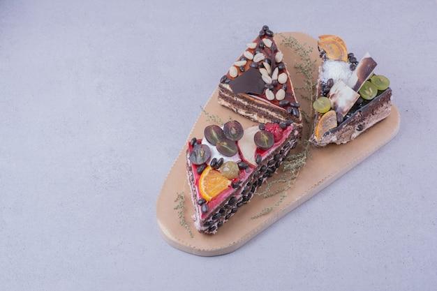 Fatias de bolo triangular com chocolate e frutas em uma placa de madeira