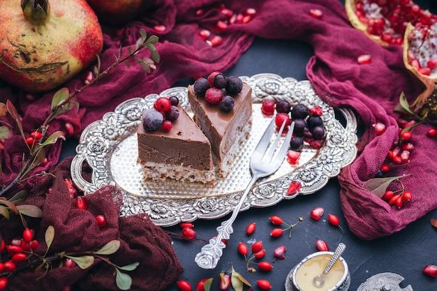 Fatias de bolo vegano em uma placa de metal com frutas vermelhas no topo