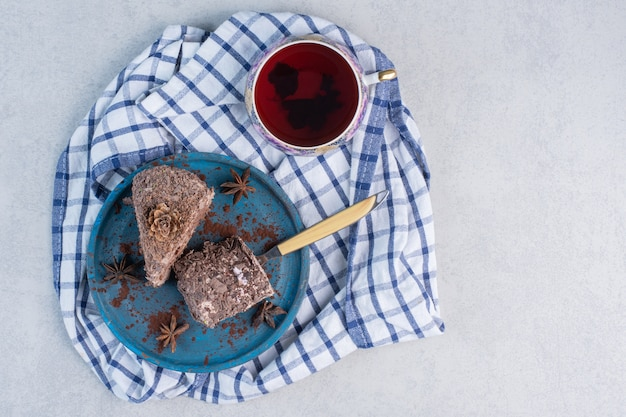 Fatias de bolos em uma travessa ao lado de uma xícara de chá na mesa de mármore.