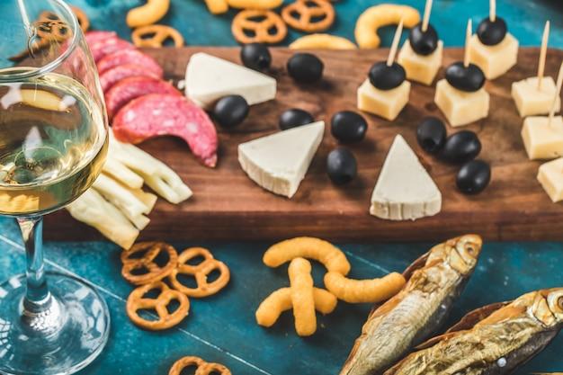 Fatias de calabresa, queijo e azeitonas pretas em uma placa de madeira com biscoitos e um copo de vinho branco