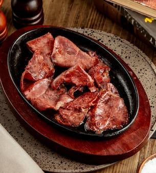Fatias de carne cozida crua, servidas em panela de ferro fundido