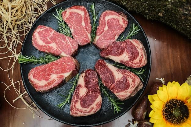 Fatias de carne crua colocadas na frigideira com ervas