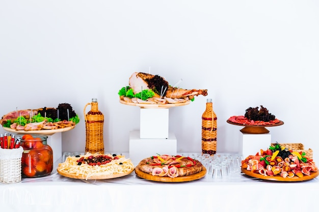 Fatias de carne de porco em pratos de madeira e bebida recepção de casamento