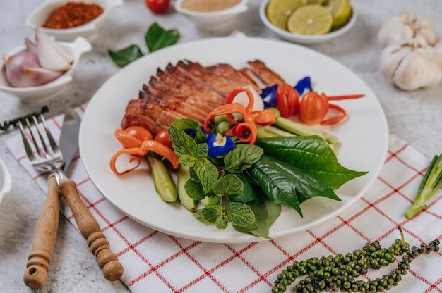 Fatias de carne de porco frita com limão, cebola, cebola roxa, tomate, feijão comprido, ervilha-borboleta flor e hortelã.