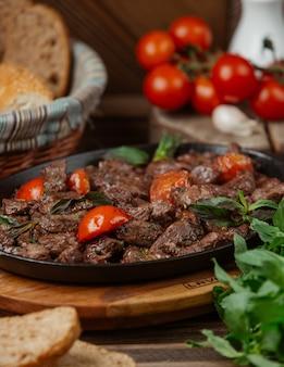 Fatias de carne marinadas, guarnecidas com estragão e tomate